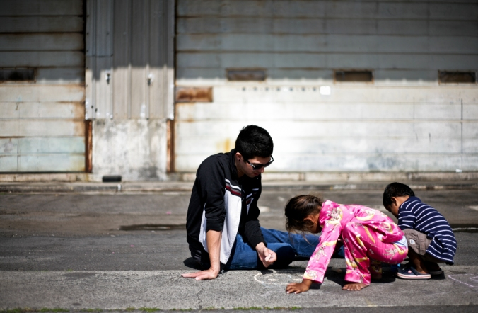 A university student helps two children draw an outline of a sidewalk chalk game.