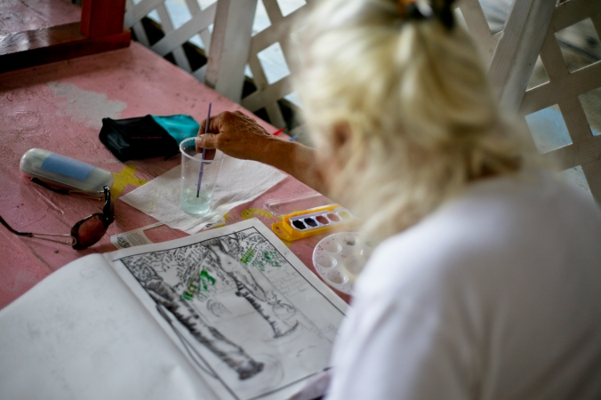 A woman who lives at the shelter uses donated watercolor supplies to create a piece of art.