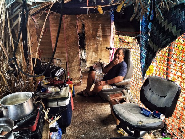 Sam resting in a friend's makeshift shelter in Kaka'ako.