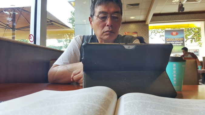 My father reading the news, while I study for class.